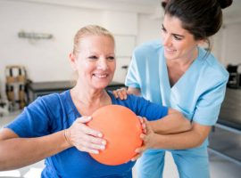 Senior woman patient at physical recovery therapy exercising with a ball and therapist helping her while both are smiling very happy